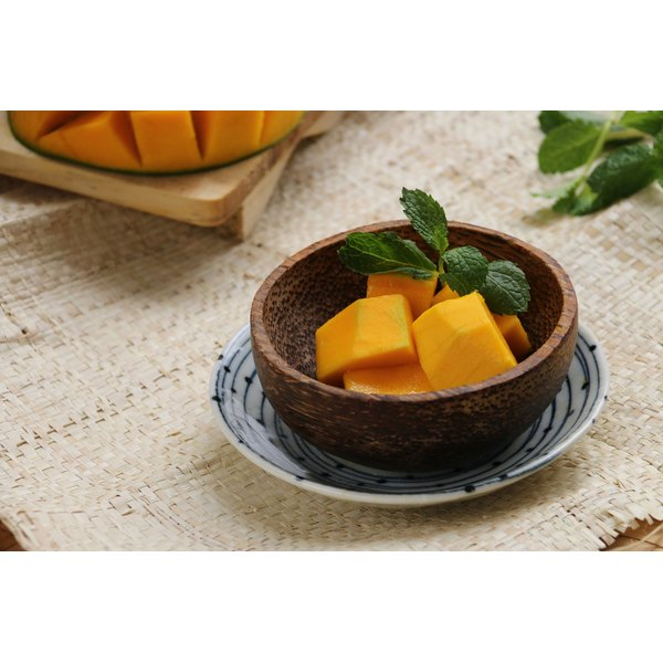 A bowl of cubed mangos sits on a table in a tropical setting.