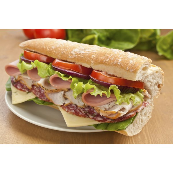 A sub sandwich on a large loaf of bread.