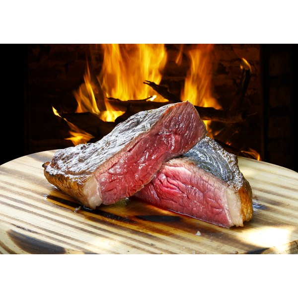 A pair of grilled steaks in front of an open flame.