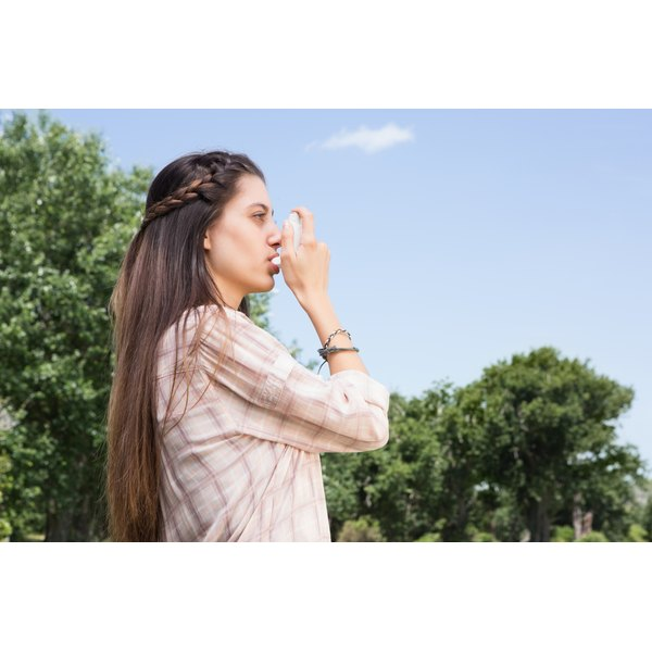 Young woman using her inhaler on a sunny day