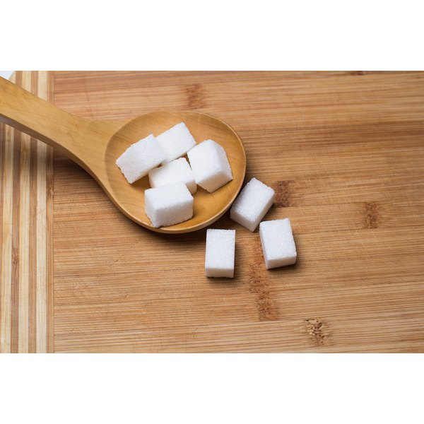 Sugar cubes on a wooden spoon.