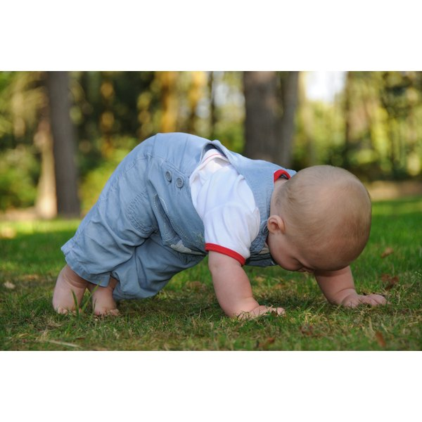 A baby is learning to crawl in a park on a sunny day.