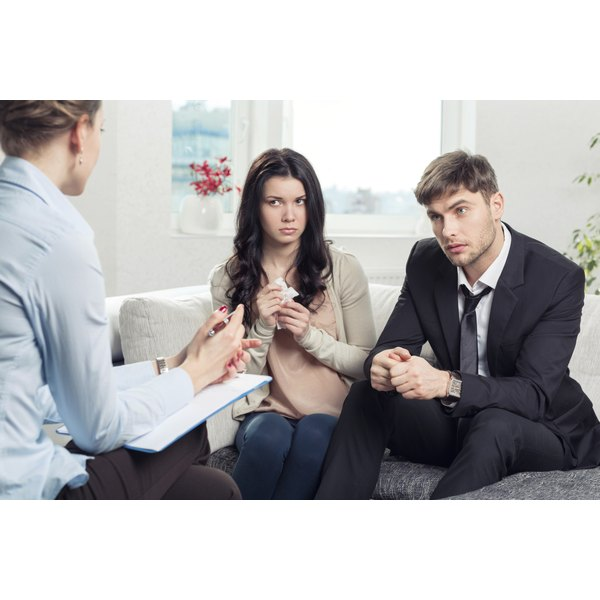A married couple on a couch talk to a therapist.