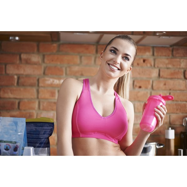A fitness woman is holding a shaker bottle.