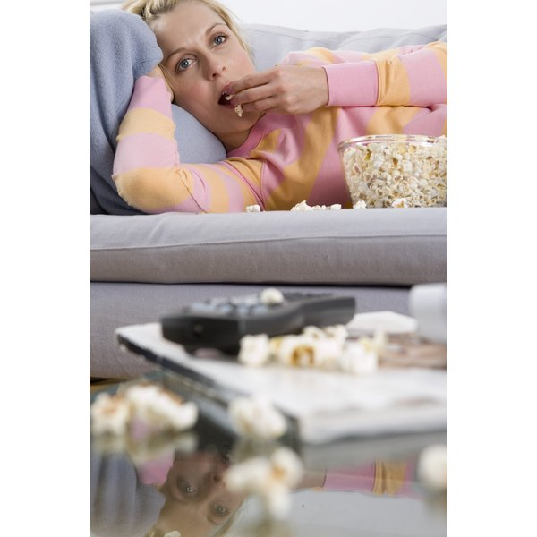 Woman eating popcorn while watching television.