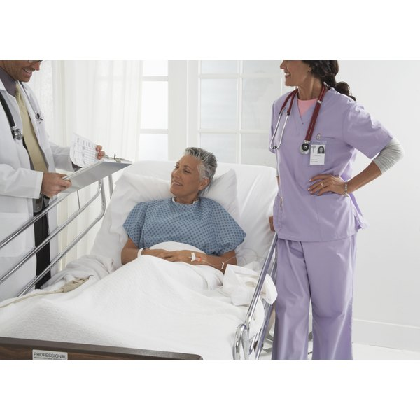 A woman is lying in a hospital bed talking to a nurse and doctor.