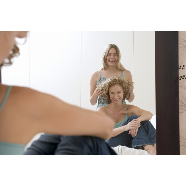 A teenage girl playing with her mother's hair in the mirror.