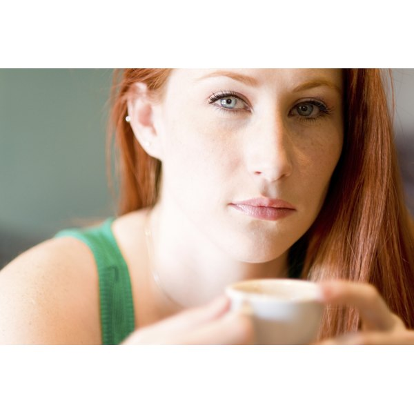 A woman is holding an espresso shot.