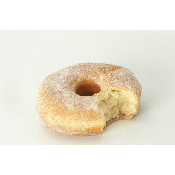 A sugar covered doughnut with a bite taken out of it.