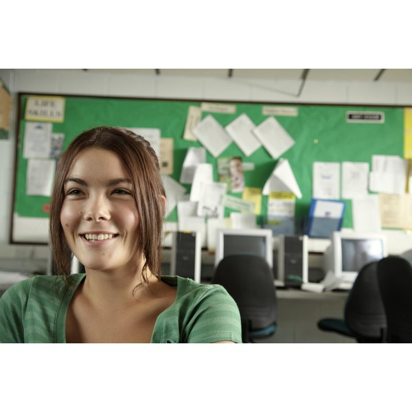 A teenage girl smiles as she sits in a classroom.