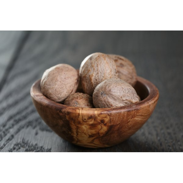 A bowl of whole nutmeg on a wooden table.