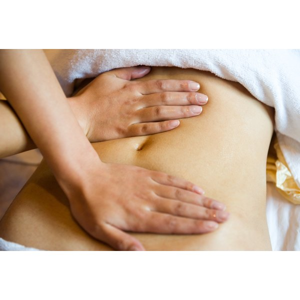 Close up on a woman's abdomen while she gets a massage.