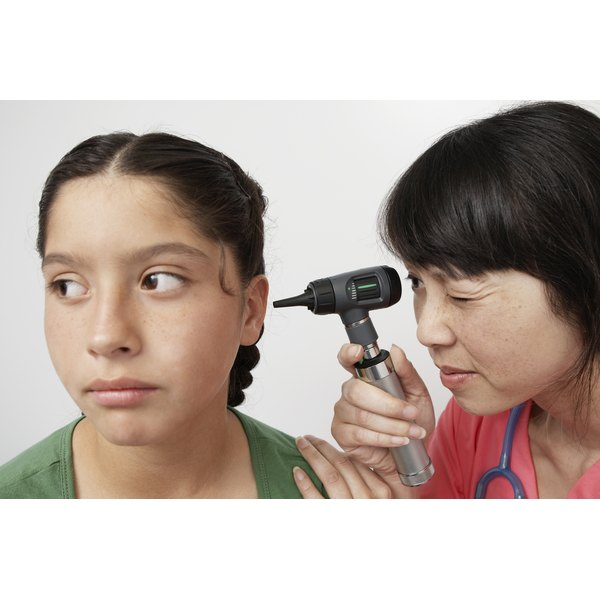 Doctor examining a young girl's ear