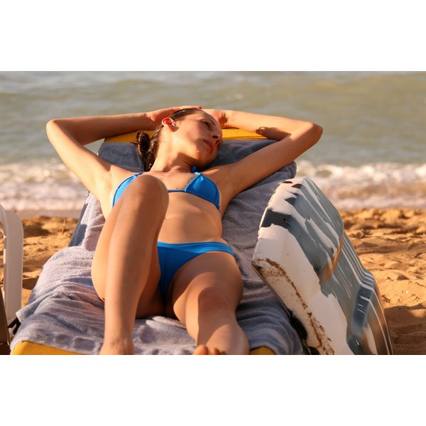 A woman sunbathing on the beach in a lounge chair.