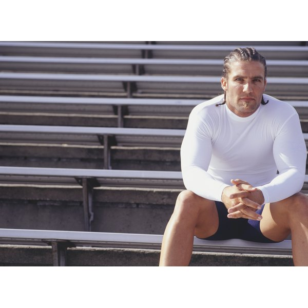 A muscular man is sitting on some bleachers.