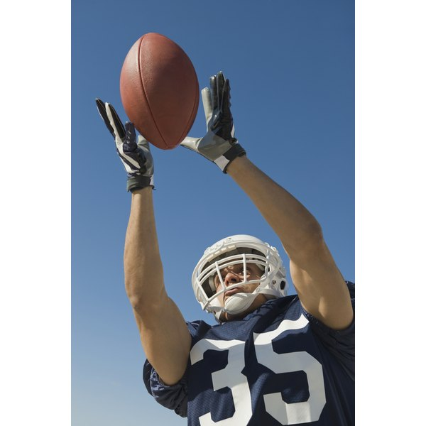 Close-up of man catching football while wearing gloves.