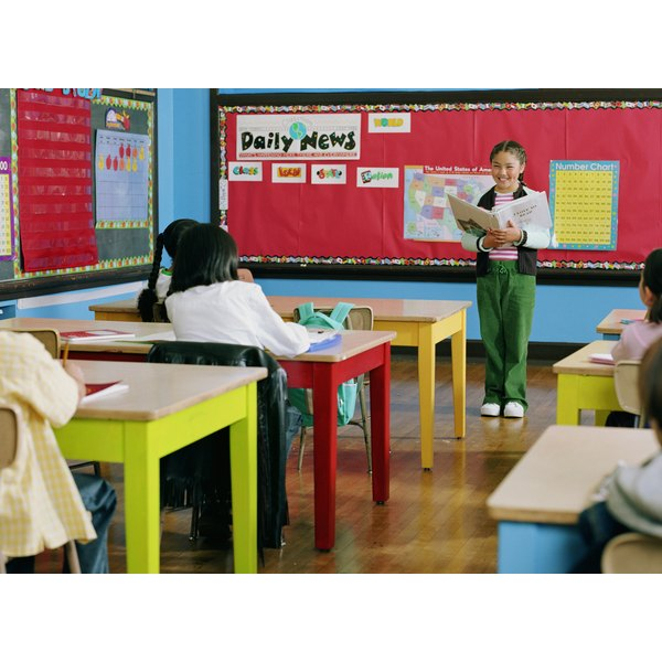 Girl standing on front of her classroom preparing to give presentation.