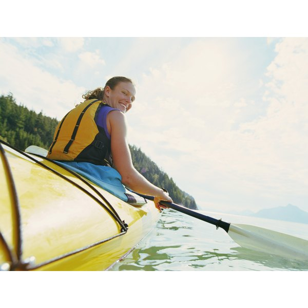A woman in a kayak smiles as she paddles on a lake.