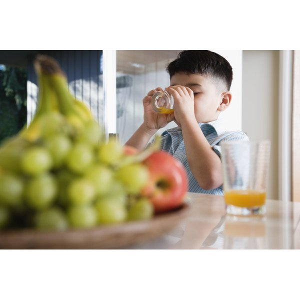 A boy is drinking juice from a glass.