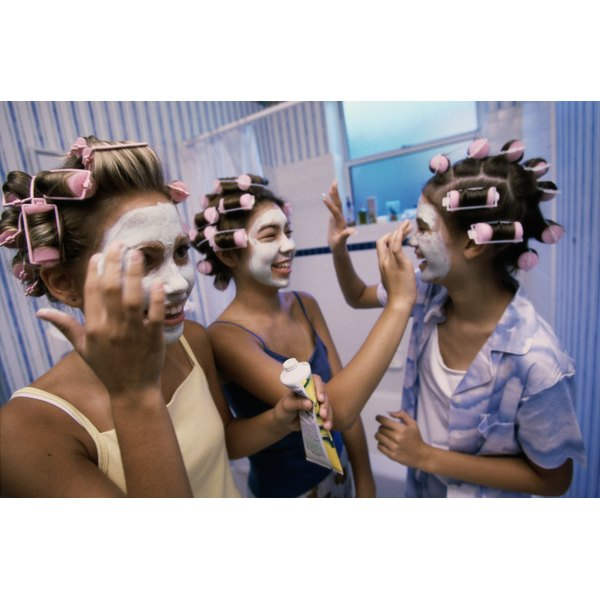 Teenagers apply facial masks during a sleep over.