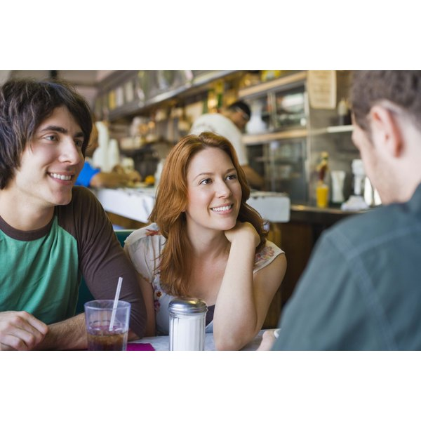 Positive people engaging in conversation at a cafe.