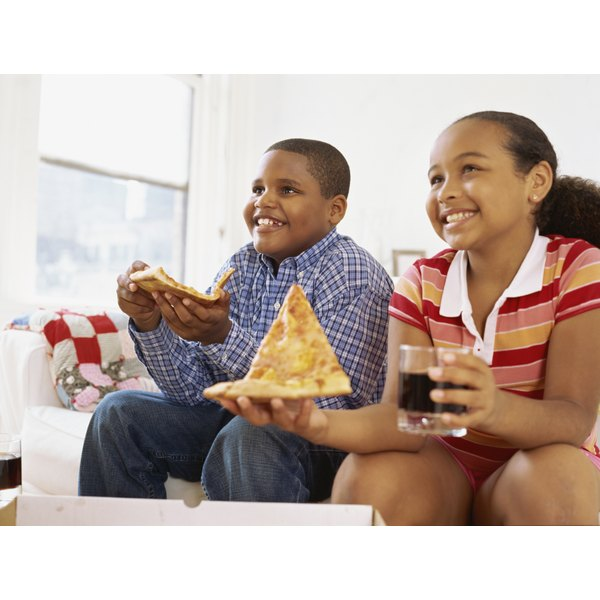 Young kids are eating slices of pizza.