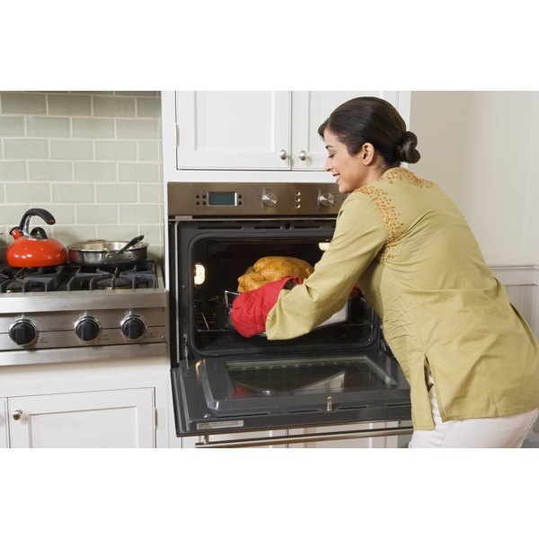 A woman is pulling a turkey out of the oven.