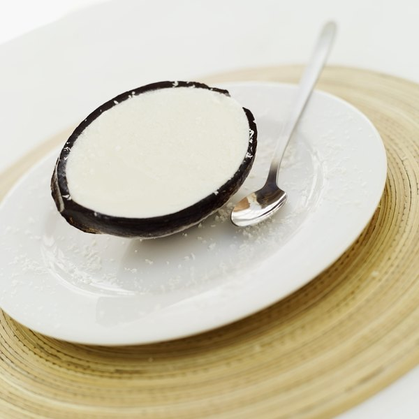 Half of a coconut sitting on a plate, next to a spoon.