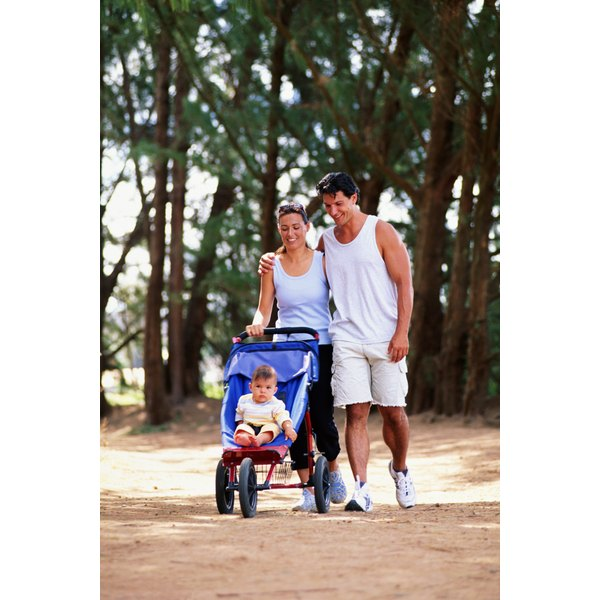 Parents hiking with child in jogging stroller.