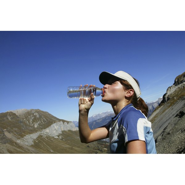 A woman is drinking form a blue bottle.