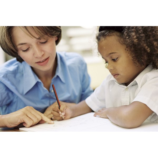 teacher teaching child how to write