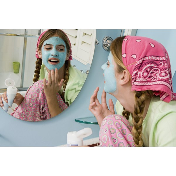 A young girl doing a facial at home.