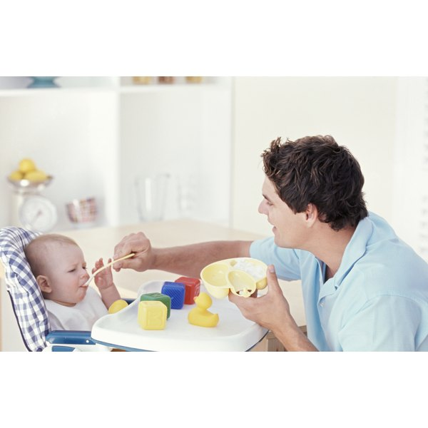 A father feeds his young baby sitting in a high chair.