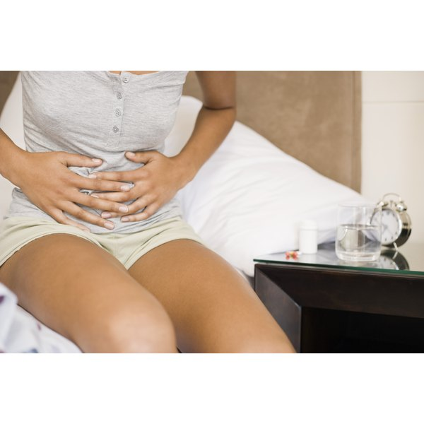 A woman experiences stomach pain.