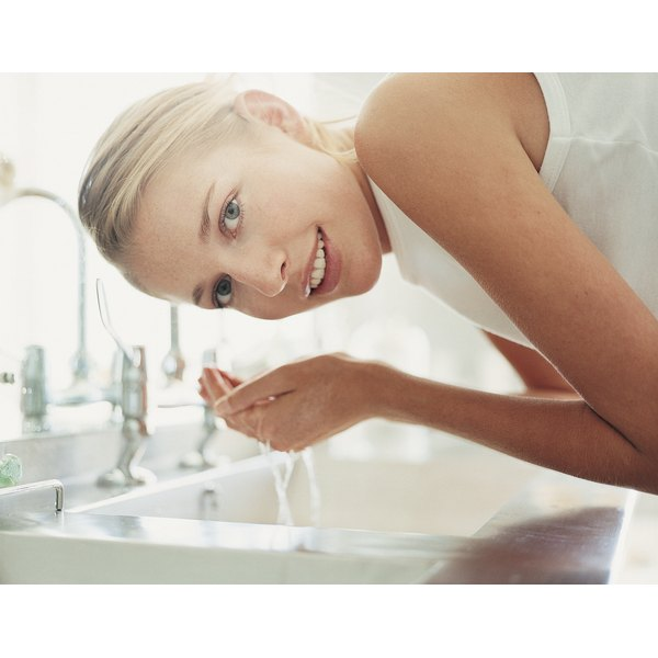 A woman washes her face over a bathroom sink.