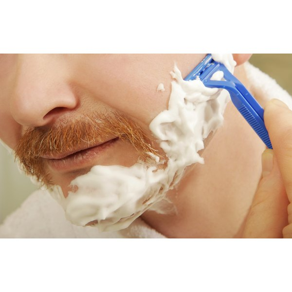 Close-up of a man with a ginger moustache shaving with a plastic razor.