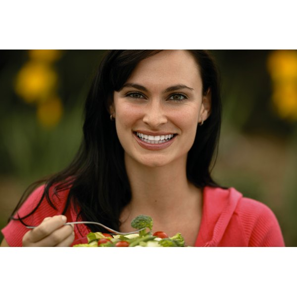 A woman is eating a salad.