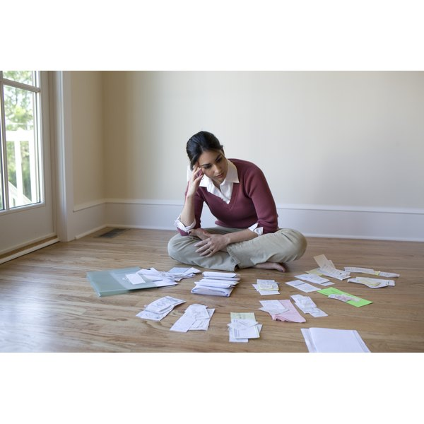 A woman organizing financial documents and receipts on the floor.