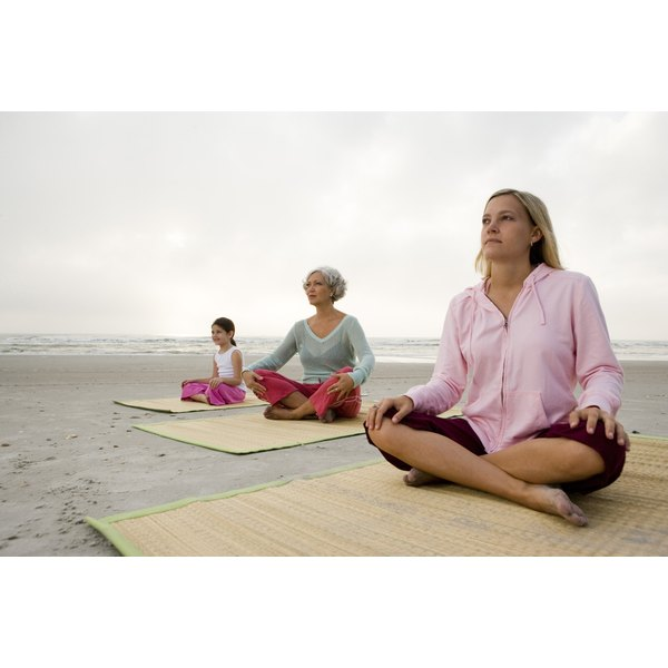 Three women practicing yoga on the beach.
