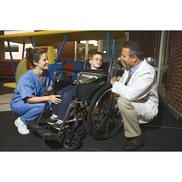 A doctor and nurse talking to a child in a wheelchair.