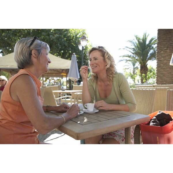 Two women talking to each other at a table.