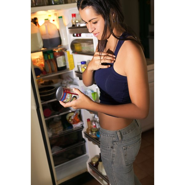Teenage girl reading nutrition label on food.
