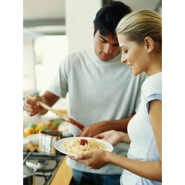 fit man and woman prepare plate of pasta in their kitchen