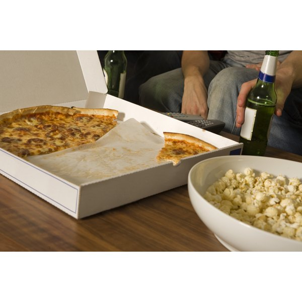A close-up of a box of pizza, bowl of popcorn, and bottle of beer.