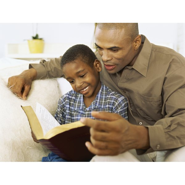 A young boy reading the Bible with his father.