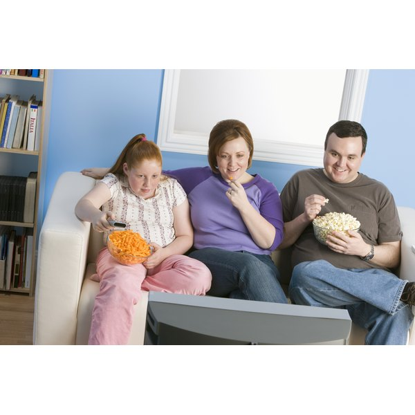 An overweight family is sitting on the couch.