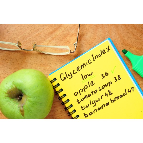 An apple next to a notepad with Glycemic Index and foods listed on it.