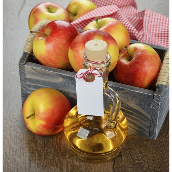 A small jar of Apple cider vinegar next to a box of apples.