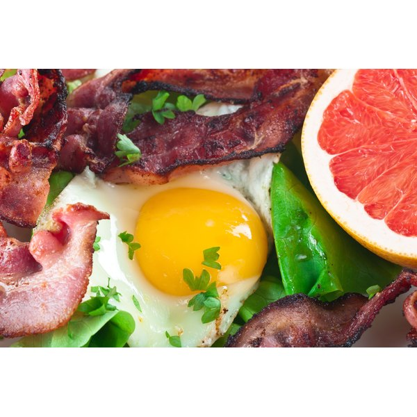 A close-up of eggs, bacon, greens and grapefruit.