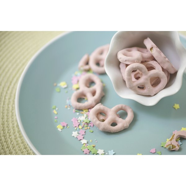 A plate and dish holding strawberry yogurt coated pretzels.
